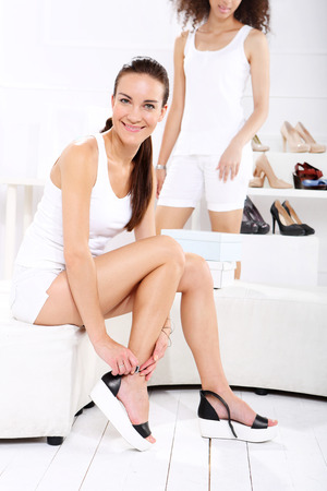 wedges: Shopping in a boutique, women buy shoes