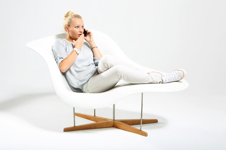 Blonde talking on mobile phone while sitting on a stylish white chair photo