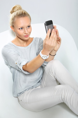 hone: Blonde talking on mobile phone while sitting on a stylish white chair
