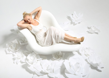 sensual massage: Beautiful young woman sitting on a white chair surrounded by stylish white flowers