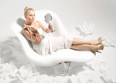 girl shoes: Beautiful young woman sitting on a white chair surrounded by stylish white flowers