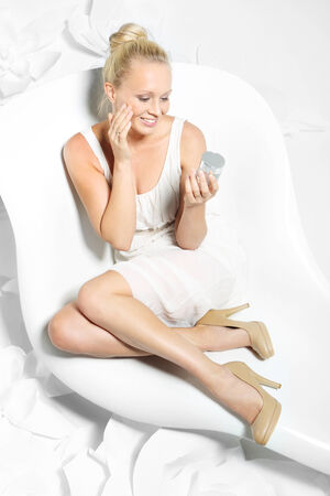 Beautiful young woman sitting on a white chair surrounded by stylish white flowers photo