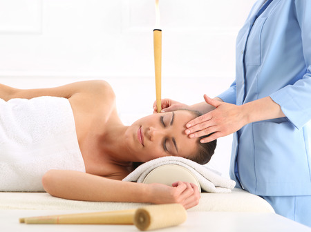 human ear: Woman relaxes in the study of natural medicine ear candling treatment.