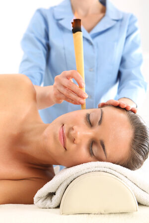 pinna: Woman relaxes in the study of natural medicine ear candling treatment.
