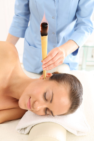 pinna: Woman relaxes in the study of natural medicine. ear candling treatment.