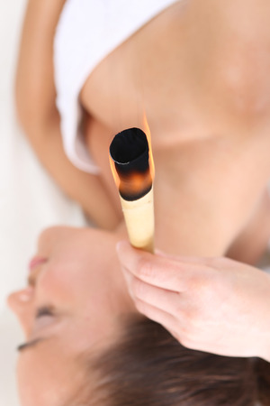 Woman relaxes in the study of natural medicine ear candling treatment. photo