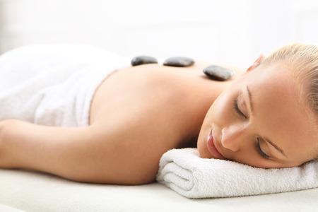 salon de belleza: Mujer rubia atractiva en el sal�n de spa en piedras de masaje de relajaci�n de basalto