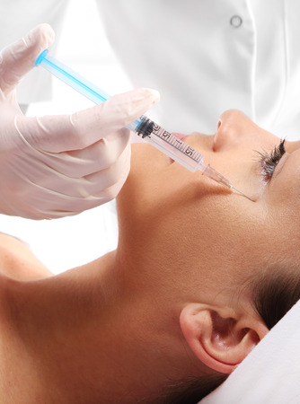 cosmetologies: Caucasian woman during surgery using a scalpel