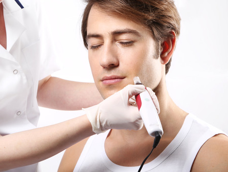 attaches: Handsome man during microdermabrasion treatment in beauty salon