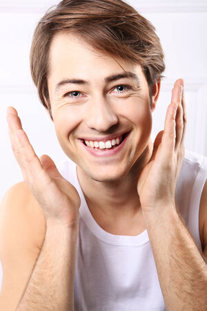 Young handsome man after shave balm is applied on the skin face