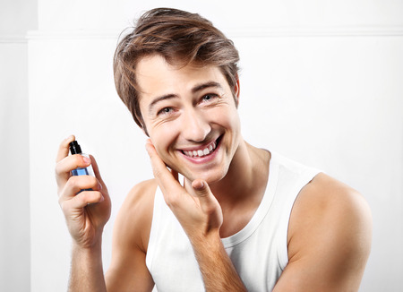 Young handsome man after shave balm is applied on the skin face photo