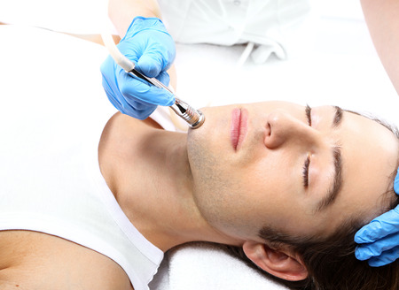 dermatologist: Portrait of a young man groomed during the treatment in the beauty salon