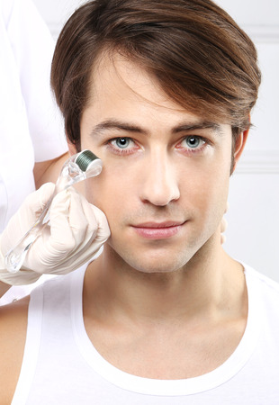 Portrait of a young man groomed during the treatment in the beauty salon