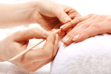 nail file: Manicure, pushing skins, a woman to a beautician Stock Photo