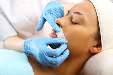 depilation: Depilation with hot wax mustache in the beauty salon Stock Photo