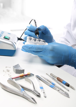 prosthodontics: Prosthetics hands while working on the denture, false teeth, a study and a table with dental tools.