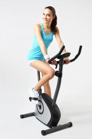 Entrenamiento de la mujer joven en una bicicleta estática mientras se escucha música