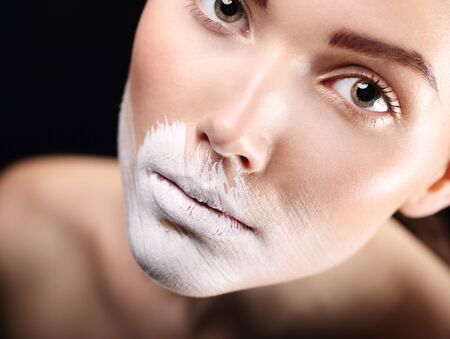 body painting: Body painting, fancy makeup. Portrait of a beautiful woman with lips painted over with white paint. Stock Photo