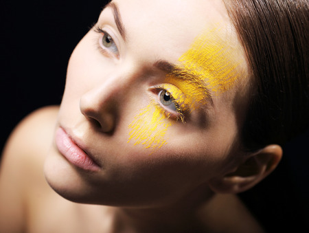 characterization: Artistic makeup, expression, imagination.Portrait, close-up on the face of a woman in a fancy makeup.