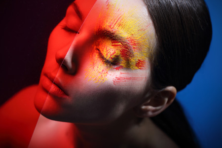 characterization: Hot red, sunny yellow, fancy makeup.Portrait, close-up on the face of a woman in a fancy makeup. Stock Photo