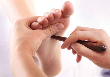 acupressure: Foot reflexology. Natural medicine, reflexology, acupressure foot massager oppresses energy flow points Stock Photo