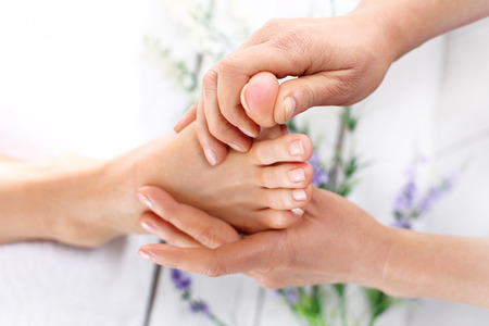 fußsohle: Reflexzonenmassage. Frau in einem Schönheitssalon für Pediküre und Fußmassage.
