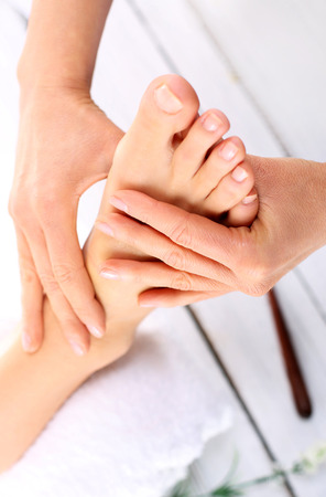 pressure massage: Reflexology. Woman in a beauty salon for pedicure and foot massage.