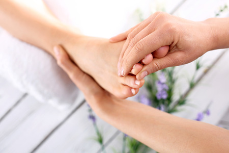 foot pain: Summer foot care. Woman in a beauty salon for pedicure and foot massage. Stock Photo