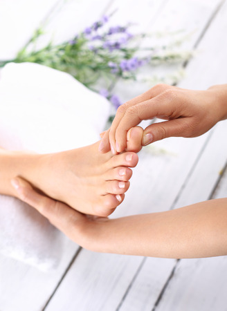 flat foot: Help for tired feet. Woman in a beauty salon for pedicure and foot massage.