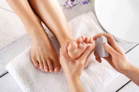 french pedicure: Scrub, scrub with pumice dead epidermis. Foot care treatment and nail, the woman at the beautician for pedicure.