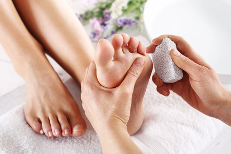 french pedicure: Peeling feet pedicure treatment. Foot care treatment and nail, the woman at the beautician for pedicure. Stock Photo
