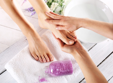 acupressure hands: Prepare feet before the summer. Woman in a beauty salon for pedicure and foot massage.