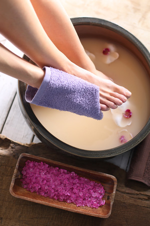 Washing of feet. A woman washes the feet in a bowl of water and salt to the foot