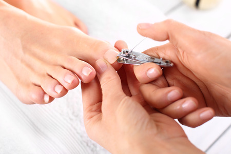 pink nail polish: Trimming toenails, woman on pedicure Stock Photo