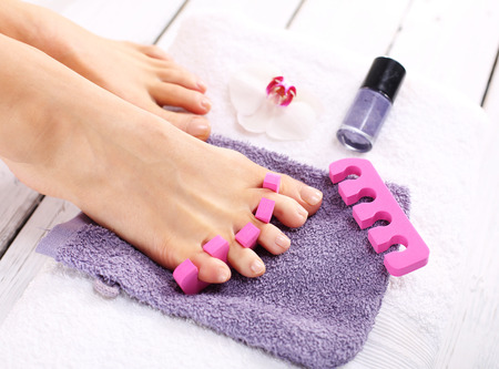 Purple pedicure, groomed female foot