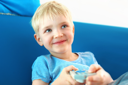 on looker: The boy is changing the channel on the TV using the remote control Stock Photo