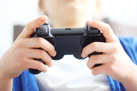 console: Gamepad, video game. Child holding a remote control in his hand video games.