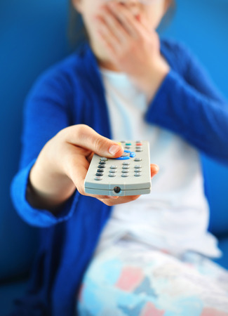 looker: Switch off. Child with tv remote control Stock Photo