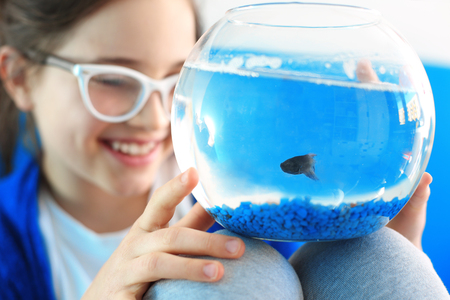 pet fish: Child holding a crystal ball with blue a fish