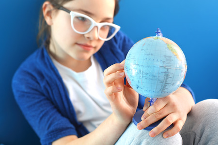 invents: The girl shows a finger on the globe
