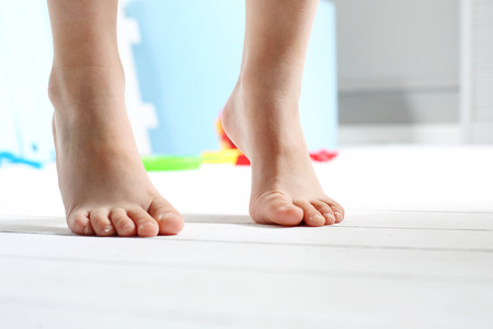 Childrens feet. Childs feet on the wooden floor