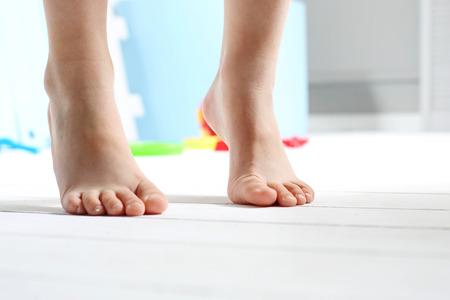 Dzieciak bose stopy. Childs bose stopy na drewnianej podłodze