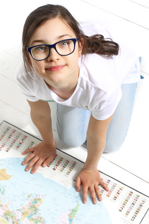 invents: Summer travel plan. The girl shows a finger on the world map the direction of the summer expedition Stock Photo