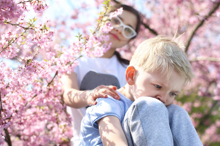 comforted: Keep your head up it will be well Children sitting under a blooming tree sister comforted by his brother