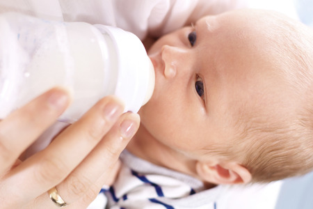nursing bottle: infant nutrition. A woman feeds a newborn with modified milk from a bottle