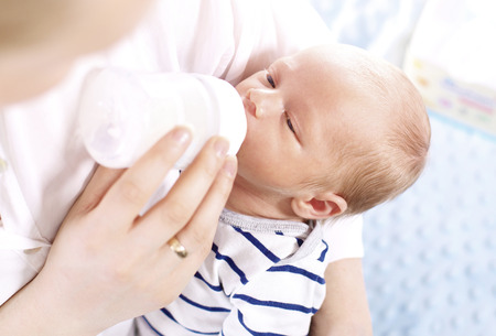 Bottlefed baby. A woman feeds a newborn with modified milk from a bottle