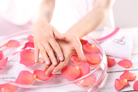 Smooth leather palm beauty treatment clinic.Treatment hand and nail care women hold hands vial of rose oil over the bowl with rose petals