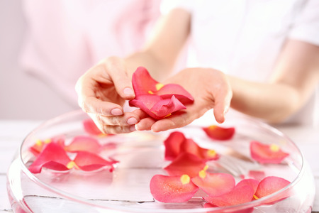 Hands women rose bath nursing.Care treatment of hands and nails woman hands over the bowl with rose petals