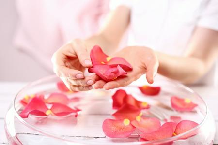 reflexologie plantaire: Mains des femmes ont augmenté de bain traitement nursing.Care des mains et des ongles femme les mains sur le bol de pétales de roses Banque d'images
