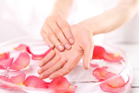 reflexologie: Réflexologie et main douce de traitement de massage.Care des mains et des ongles femme les mains sur le bol de pétales de roses
